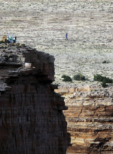 """FILE - In this June 23, 2013, file photo, daredevil Nik Wallenda crosses a tightrope 1,500 feet above the Little Colorado River Gorge, Ariz., on the Navajo Nation outside the boundaries of Grand Canyon National Park. When actor Will Smith turns 50 on Tuesday, Sept. 25, 2018, he will jump head-first into the big milestone. The """"Fresh Prince"""" plans to bungee jump from a helicopter over a gorge just outside Grand Canyon National Park. His birthday activity is the latest in a vast history of outrageous stunts staged in and around one of the world's seven natural wonders. (AP Photo/Rick Bowmer, File)"""