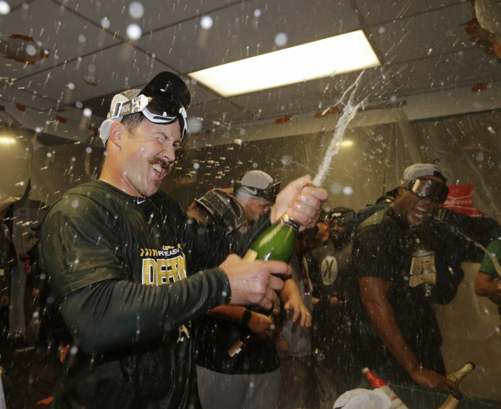 Oakland Athletics' Daniel Mengden celebrates in the clubhouse after clinching a wild card spot after the baseball game against the Seattle Mariners, Monday, Sept. 24, 2018, in Seattle. (AP Photo/John Froschauer)