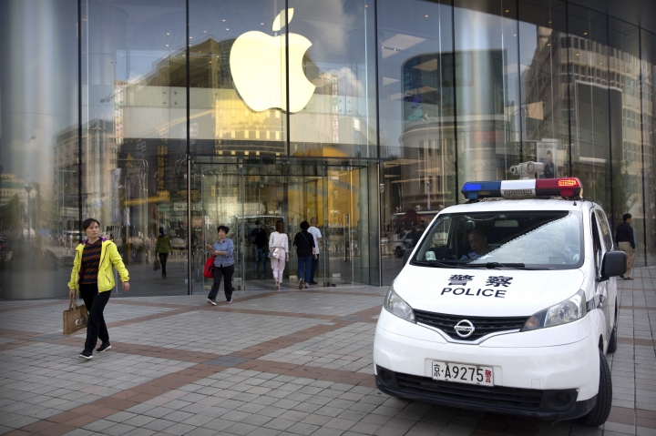"Chinese police sit in their vehicle as it is parked outside an Apple store at an outdoor shopping area in Beijing, Tuesday, Sept. 25, 2018. A Chinese trade envoy said Tuesday that talks with Washington are impossible while the United States ""holds a knife"" to Beijing's neck by imposing tariff hikes. (AP Photo/Mark Schiefelbein)"