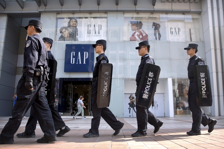 """Chinese police patrol in formation past a store from American clothing retailer Gap at an outdoor shopping area in Beijing, Tuesday, Sept. 25, 2018. A Chinese trade envoy said Tuesday that talks with Washington are impossible while the United States """"holds a knife"""" to Beijing's neck by imposing tariff hikes. (AP Photo/Mark Schiefelbein)"""