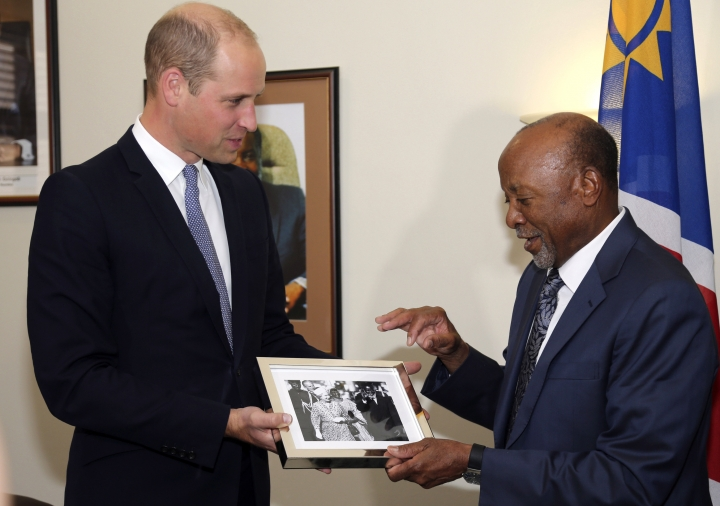 Britain's Prince William, left, presents Namibia's Vice President Nangolo Mbumba with a photo of his grandmother Queen Elizabeth with Namibia's first President, Sam Nujoma, in Windhoek, Namibia, Monday Sept. 24, 2018. The prince is on a two day visit to the southern African state with the focus being on the illegal wildlife trade as an organized crime, building coalitions and closing down markets for illicit wildlife products. (AP Photo/Dirk Heinrich)