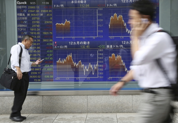People walk by an electronic stock board of a securities firm in Tokyo, Tuesday, Sept. 25, 2018. Asian stock markets were mostly lower Tuesday after a Chinese government report accusing the Trump administration of bullying other countries dampened hopes for a settlement in their escalating tariff war. (AP Photo/Koji Sasahara)