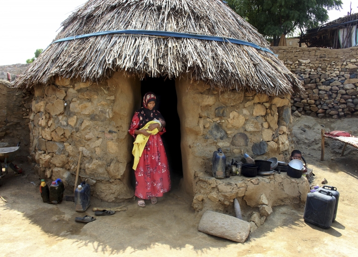 In this Sept. 22, 2018 photo, Amna Ali, mother of 3-year-old Zaifa Shouib, who was the fifth child known to have died in the district this year of malnutrition-related illness, stands in front of her hut holding a baby in Khayran al-Maharq, Hajjah, Yemen. At a local medical facility which did not have enough supplies, Zaifa's father was told she had to be taken to a hospital further away to treat kidney complications. He had no way to pay for transportation there. (AP Photo/Hammadi Issa)
