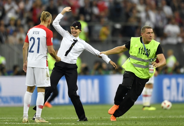 FILE - In this Sunday, July 15, 2018 file photo, stewards pull a woman off the pitch after she stormed onto the field and interrupted the final match between France and Croatia at the 2018 soccer World Cup in the Luzhniki Stadium in Moscow, Russia. The chief organizer of Russia's World Cup says police stopped 170 people from invading the pitch during games before four members of the Pussy Riot protest group eventually stormed the final dressed as police officers. Organizing committee CEO Alexei Sorokin has downplayed security problems despite the pitch invasion that happened in the final between France and Croatia on July 15. (AP Photo/Martin Meissner, File)