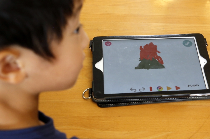 In this July 12, 2018, photo, a child works on a digital program at Coby Preschool in Yoshikawa, suburban Tokyo, on an assignment, which was to draw on a triangle on an iPad. For the kids, it's all about having fun. Japanese preschool programs equipped with tablet computers aim to prepare kids for the digital age. (AP Photo/Yuri Kageyama)