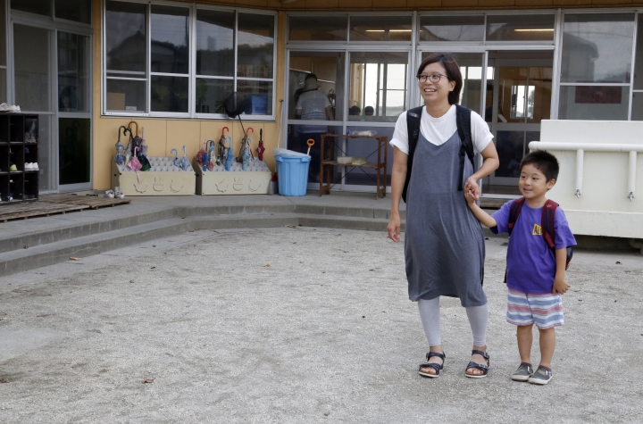 In this July 12, 2018, photo, Masami Uno, a hospital worker, picks up her children, 5-year-old Ayumu, right, and his 2-year-old sister, not in the picture, at Coby Preschool in Yoshikawa, suburban Tokyo. For the kids, it's all about having fun. Japanese preschool programs equipped with tablet computers aim to prepare kids for the digital age. (AP Photo/Yuri Kageyama)