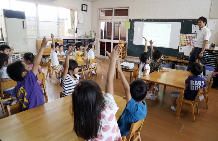 In this July 12, 2018, photo, children raise their hands to share views as they take part in a digital program at a Coby Preschool in Yoshikawa, suburban Tokyo, with their teacher and preschool principal Akihito Minabe. For the kids, it's all about having fun. Japanese preschool programs equipped with tablet computers aim to prepare kids for the digital age. (AP Photo/Yuri Kageyama)