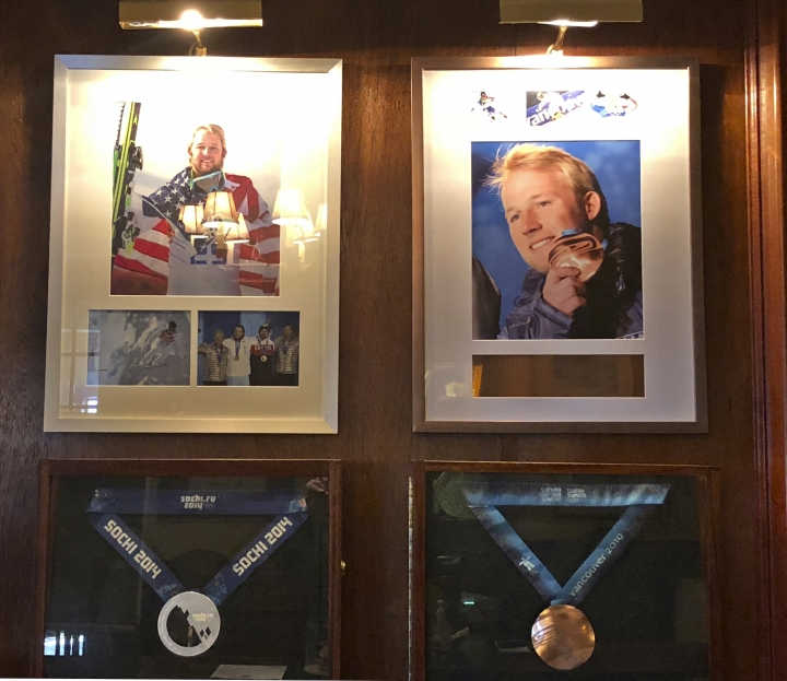 In this Sept. 1, 2018, photo, Olympic silver and bronze medals won by former U.S. skier Andrew Weibrecht hang behind the front desk of the Mirror Lake Inn in Lake Placid, New York. The 32-year-old Weibrecht retired in May to spend more time with his young family and learn the business of operating the inn, that his parents have owned since the 1970s. (AP Photo/John Kekis)