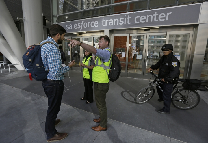 "Mike Eshleman, with AC Transit, directs people away from the Salesforce Transit Center following its closure, Tuesday, Sept. 25, 2018, in San Francisco. San Francisco officials shut down the city's celebrated new $2.2 billion transit terminal Tuesday after discovering a crack in a support beam under the center's public roof garden. Coined the ""Grand Central of the West,"" the Salesforce Transit Center opened in August near the heart of downtown after nearly a decade of construction. It was expected to accommodate 100,000 passengers each weekday, and up to 45 million people a year. (AP Photo/Eric Risberg)"