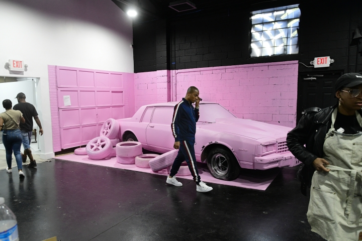 This Sept. 14, 2018 photo shows rapper Clifford Harris Jr., better known as T.I., next to a car once owned by 2 Chainz and converted into an exhibit for Trap Music Museum in Atlanta. The rapper is paying homage to the trap music culture with its own museum dedicating areas of the exhibit to rappers including himself, Gucci Mane, Jeezy, Rick Ross and Future. The museum opens on Sept. 30. Trap is a popular sub genre of hip-hop with the term trap referring to places where drug deals take place. (AP Photo/John Amis)