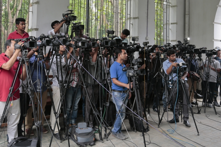 FILE- In this May 3, 2016 file photo, Bangladeshi journalists cover proceedings outside a court in Dhaka, Bangladesh. Journalists and human rights groups are demanding major amendments to a new law passed in Bangladesh Parliament in September, 2018, saying the law will choke constitutional rights of freedom of speech and expression. (AP Photo/A.M. Ahad, File)