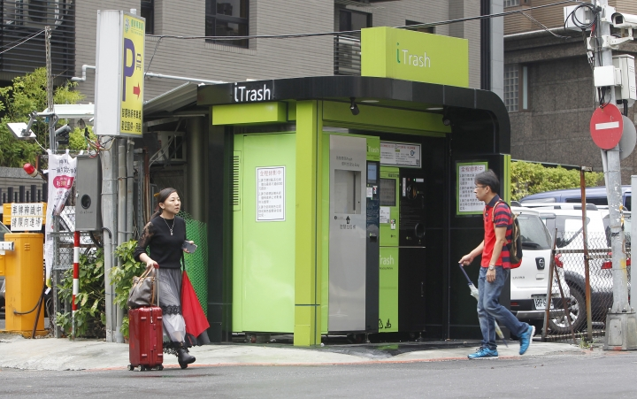 People walk pass by an iTrash booth at an intersection in Taipei, Taiwan, Friday, Sept. 28, 2018. Taiwan's garbage recycling is getting smarter with a system that refunds cash credit to users when they recycle empty bottles. (AP Photo/Chiang Ying-ying)