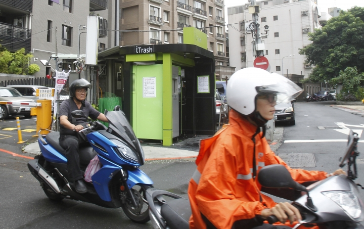 """A woman rides pass by an """"iTrash booth"""" at an intersection in Taipei, Taiwan, Friday, Sept. 28, 2018. Residents of Taiwan's capital Taipei are using newly installed machines called """"iTrash booths"""" to recycle cans and bottles in exchange for credit on their transportation smart cards. The initiative seeks to promote recycling while also giving residents more flexibility in how they dispose of their garbage. (AP Photo/Chiang Ying-ying)"""