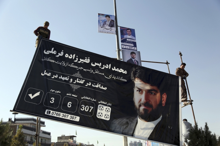 Afghan men installs election posters of parliamentarian candidates during the first day of elections campaign in Kabul, Afghanistan, Friday, Sept. 28, 2018. An Afghan official says that Afghan parliamentarian candidates started their campaigning across the country for the upcoming election scheduled for Oct. 20. (AP Photo/Rahmat Gul)