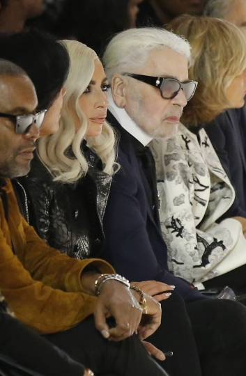Singer Lady Gaga, centre, and designer Karl Lagerfeld, right, watch the Celine Spring/Summer 2019 ready to wear fashion collection presented in Paris, Friday, Sept. 28, 2018. (AP Photo/Michel Euler)