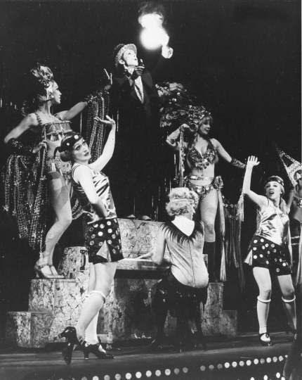 """FILE - In this Nov. 1966 file photo, Joel Grey, in the role of Master of Ceremonies, stands on the piano during the """"Money Song"""" with the ensemble in the original Broadway musical """"Cabaret"""" at the Broadhurst Theatre in New York. Joe Masteroff, the Tony Award-winning story writer of the brilliant, edgy musical """"Cabaret"""" and the touching, romantic """"She Loves Me,"""" has died at age 98. The Roundabout Theatre Company, which produced recent revivals of his best-loved shows, said Masteroff died Friday, Sept. 28, 2018, at the Actors Fund Home in Englewood, N.J. (AP Photo, File)"""