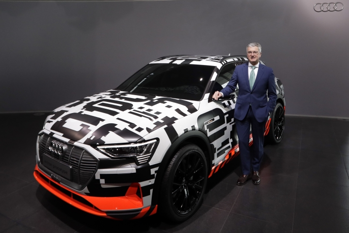 FILE - In this Thursday, March 15, 2018 file photo, Rupert Stadler, CEO of German car producer Audi, poses besides an Audi e-tron prototype car prior to the annual press conference in Ingolstadt, Germany. Doubts about diesel, Brexit, trade worries, tighter emissions controls. Those are the challenges that will be on the minds of auto executives when they gather this week ahead of the Paris Motor Show, starting with off-site events Monday, Oct. 1 followed by two days of vehicle unveilings and news conferences at the pavilion before the show opens to the public from Oct. 4 to Oct. 14. A major focus will be the rollout of luxury electric sport-utility vehicles from the established automakers competing with Tesla's all-electric Model X SUV. Daimler's Mercedes-Benz has the EQC and Volkswagen's Audi will show off the e-tron. The launches by are a notable endorsement of electric vehicles, but will they catch on with consumers? (AP Photo/Matthias Schrader, file)