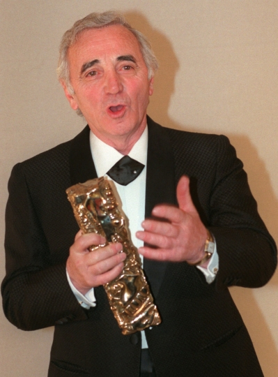 FILE - In this Feb. 8, 1997 file photo, French singer and actor Charles Aznavour holds the Honorary Cesar award as he addresses guests during the 22nd annual Cesar French film awards in Paris. Charles Aznavour, the French crooner and actor whose performing career spanned eight decades, has died. He was 94. (AP Photo/Jacques Brinon, FILE)