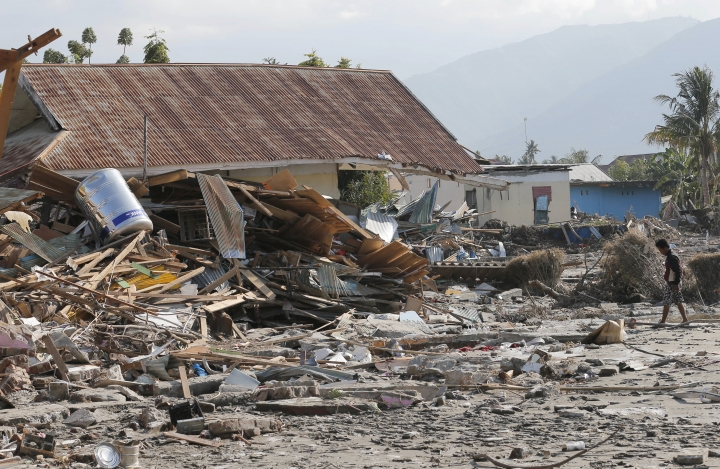 A man walks by houses damaged following a massive earthquake and tsunami at Talise beach in Palu, Central Sulawesi, Indonesia, Monday, Oct. 1, 2018. Bright-colored body bags were placed side-by-side in a freshly dug mass grave Monday, as a hard-hit Indonesian city began burying its dead from the devastating earthquake and tsunami. (AP Photo/Tatan Syuflana)