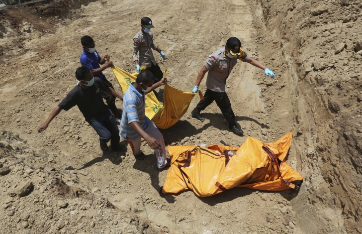 Indonesian rescue team members carry the body of a victim in a massive earthquake and tsunami to a grave during a mass burial in Palu, Central Sulawesi, Indonesia, Monday, Oct. 1, 2018. A mass burial of earthquake and tsunami victims was being prepared in a hard-hit city Monday as the need for heavy equipment to dig for survivors of the disaster that struck a central Indonesian island three days ago grows desperate. (AP Photo/Tatan Syuflana)