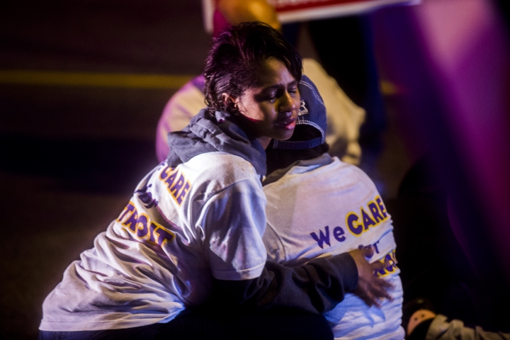 Two protestors share an embrace after one was injured when a truck collided with into protesters calling for the right to form unions Tuesday, Oct. 2, 2018, in Flint, Mich. Police said the collision appears to be an accident. (Jake May/The Flint Journal via AP)