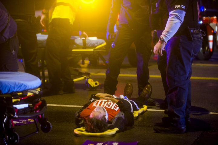 A protester lies on a backboard in the street after a truck collided with into protesters calling for the right to form unions Tuesday, Oct. 2, 2018, in Flint, Mich. Police said the collision appears to be an accident. (Jake May/The Flint Journal via AP)