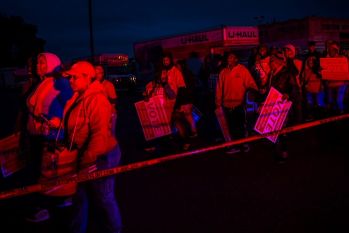 Light from police vehicles shine on protesters as they walk around police tape after a truck collided with into protesters calling for the right to form unions Tuesday, Oct. 2, 2018, in Flint, Mich. Police said the collision appears to be an accident. (Jake May/The Flint Journal via AP)