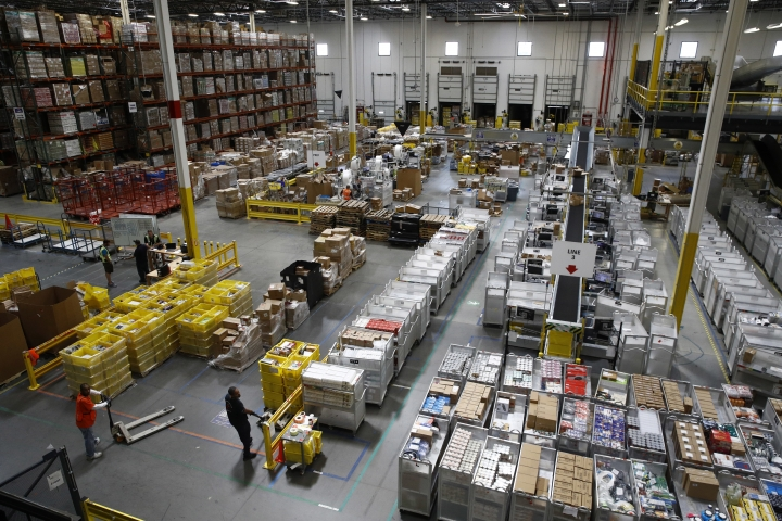 FILE- In this Aug. 3, 2017, file photo, workers prepare to move products at an Amazon fulfillment center in Baltimore. Amazon's announcement Tuesday, Oct. 2, 2018, that it will raise its minimum wage to $15 an hour will intensify the pressure on other companies to also lift their pay levels, particularly retailers and warehouse operators that are looking to staff up for the holidays. (AP Photo/Patrick Semansky, File)