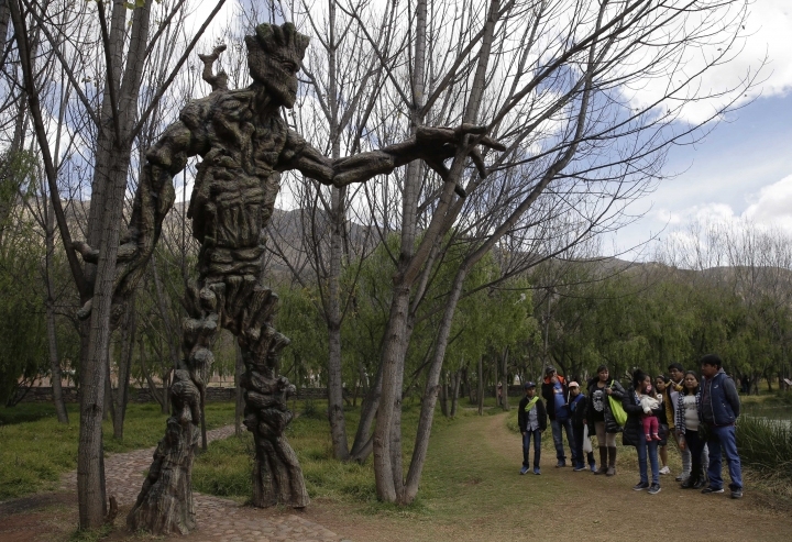 """In this Aug. 4, 2018 photo, a group of residents stand near a sculpture of Groot, a comic book superhero, at a public wetland in Cuzco, Peru. The wetland opened on May 1, and the next day got a surprise boost from afar when """"Guardians of the Galaxy"""" director James Gunn tweeted photographs of the statues. (AP Photo/Martin Mejia)"""