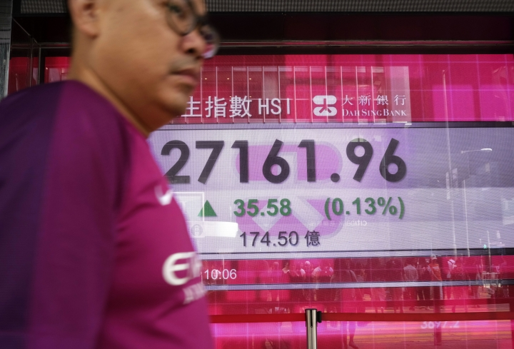A man walks past an electronic board showing the Hong Kong share index outside a local bank in Hong Kong, Wednesday, Oct. 3, 2018. Asian markets were mostly higher Wednesday on hopes that U.S. success in reaching a deal with Canada boded well for its simmering trade dispute with China. (AP Photo/Vincent Yu)