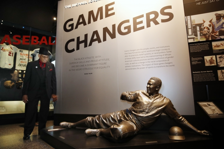 Hockey Hall of Famer Willie O'Ree, left, who was the first African-American hockey player in the NHL, looks at a statue of Jackie Robinson during a tour of the Smithsonian's National Museum of African American History and Culture, Wednesday, Oct. 3, 2018, in Washington. (AP Photo/Jacquelyn Martin)