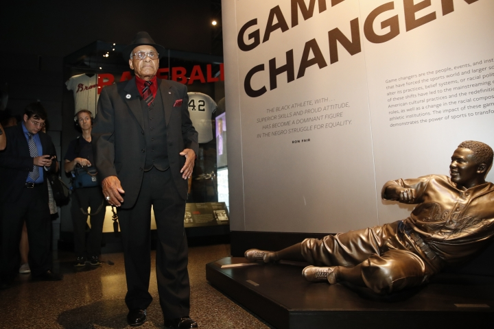 Hockey Hall of Famer Willie O'Ree, left, who was the first African-American hockey player in the NHL, walks by a statue of Jackie Robinson during a tour of the Smithsonian's National Museum of African American History and Culture, Wednesday, Oct. 3, 2018, in Washington. (AP Photo/Jacquelyn Martin)