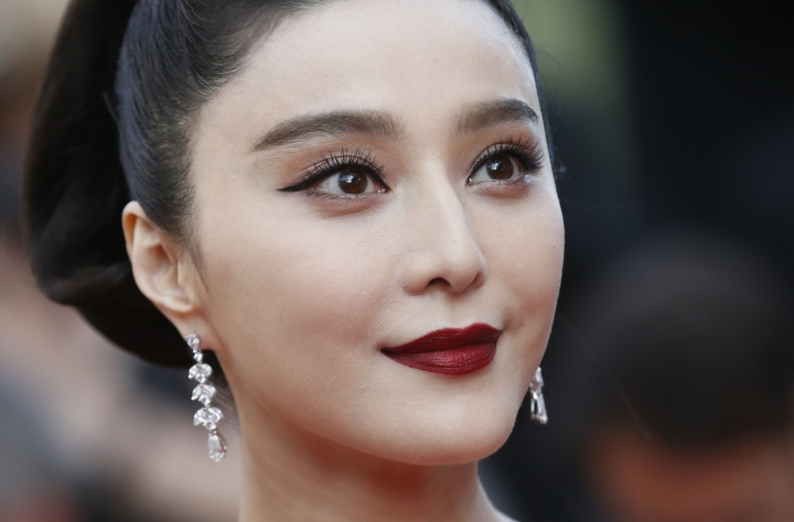 FILE - In this May 24, 2017, file photo, Fan Bingbing poses for photographers as she arrives for the screening of the film The Beguiled at the 70th international film festival, Cannes, southern France. Chinese media said on Wednesday, Oct. 3, 2018, tax authorities ordered X-Men star Fan to pay taxes and fines worth hundreds of millions of yuan but would spare her from criminal prosecution. (AP Photo/Alastair Grant, File)