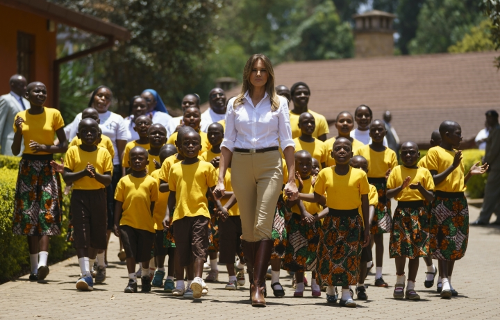 First lady Melania Trump walks with singing children as she visits the Nest Orphanage in Limuru, Kenya, Friday, Oct. 5, 2018. Melania Trump has fed baby elephants as she visits a national park in Kenya to highlight conservation efforts. The U.S. first lady also went on a quick safari. Mrs. Trump is on her first-ever visit to Africa and her first extended solo international trip as first lady. (AP Photo/Carolyn Kaster)