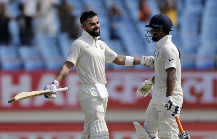 Indian cricketer Virat Kohli, left, celebrates his century with teammate Rishabh Pant during the second day of the first cricket test match between India and West Indies in Rajkot, India, Friday, Oct. 5, 2018. (AP Photo/Rajanish Kakade)