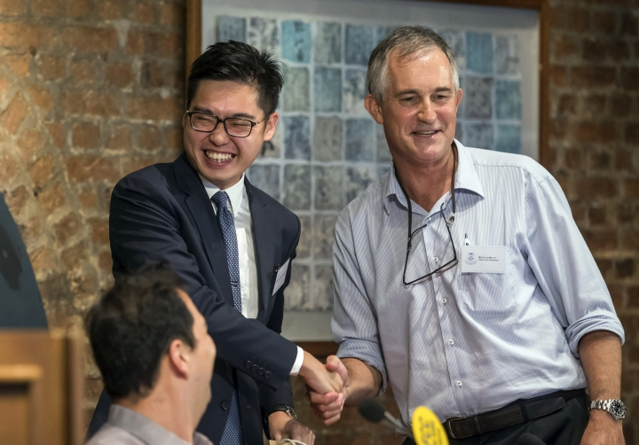 In this Aug. 14, 2018 photo, The Financial Times Asia news editor, Victor Mallet, right, shakes hands with Andy Chan, founder of the Hong Kong National Party, during a luncheon at the Foreign Correspondents Club in Hong Kong. The Financial Times said Friday, Oct. 5, 2018 that Hong Kong's government has refused to renew the work visa of Mallet, in what human rights activists say is the latest sign of a deteriorating human rights situation in the semi-autonomous Chinese territory. (Pool Photo via AP)