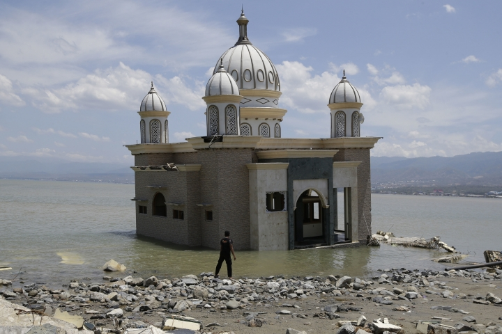 A man looks at a mosque that is isolated by water after its bridge was broken due to the massive earthquake and tsunami in Palu, Central Sulawesi, Indonesia Friday, Oct. 5, 2018. French rescuers say they've been unable to find the possible sign of life they detected a day earlier under the rubble of a hotel that collapsed in the earthquake a week ago on Indonesia's Sulawesi island. (AP Photo/Aaron Favila)