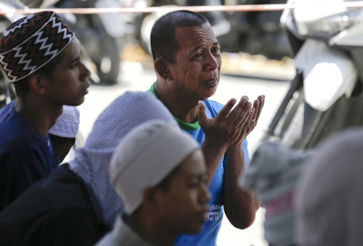 A man cries during Friday prayers outside a damaged mosque caused by the massive earthquake and tsunami in Palu, Central Sulawesi, Indonesia Friday, Oct. 5, 2018. French rescuers say they've been unable to find the possible sign of life they detected a day earlier under the rubble of a hotel that collapsed in the earthquake a week ago on Indonesia's Sulawesi island. (AP Photo/Aaron Favila)