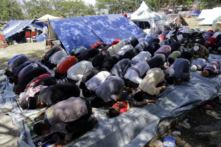 Evacuees pray near tents outside a damaged mosque caused by the massive earthquake and tsunami in Palu, Central Sulawesi, Indonesia Friday, Oct. 5, 2018. French rescuers say they've been unable to find the possible sign of life they detected a day earlier under the rubble of a hotel that collapsed in the earthquake a week ago on Indonesia's Sulawesi island. (AP Photo/Aaron Favila)