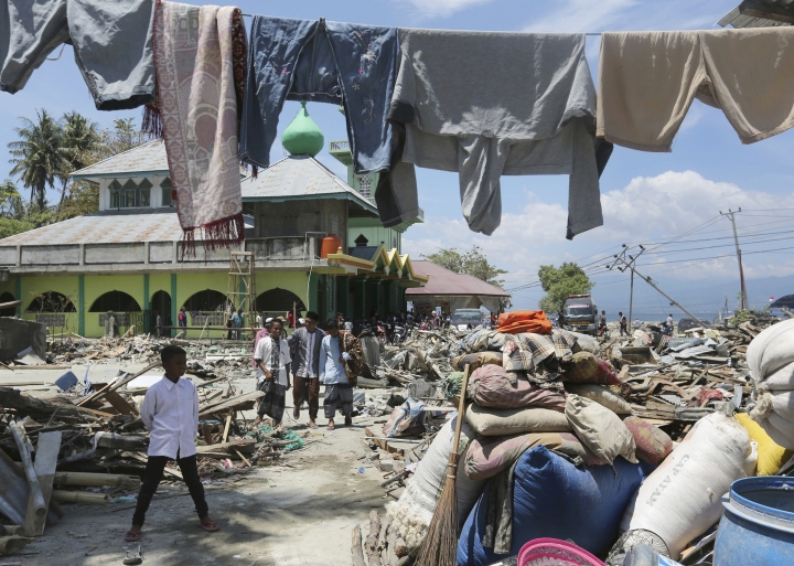 People leave after Friday prayer at a mosque amidst destruction caused by the massive earthquake and tsunami in Loly, Central Sulawesi, Indonesia Friday, Oct. 5, 2018. French rescuers say they've been unable to find the possible sign of life they detected a day earlier under the rubble of a hotel that collapsed in the earthquake a week ago on Indonesia's Sulawesi island. (AP Photo/Tatan Syuflana)