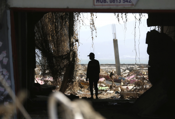 A man is silhouetted as he scavenges for usable items at a tsunami-ravaged area in Palu, Central Sulawesi, Indonesia, Friday, Oct. 5, 2018. A 7.5 magnitude earthquake rocked the city on Sept. 28, triggering a tsunami and mud slides that killed a large number of people and displaced tens of thousands others. (AP Photo/Dita Alangkara)