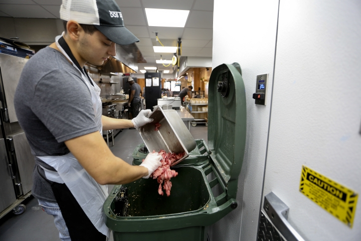 In this Aug. 22, 2018, photo, Konrad Navarrete, part of the kitchen crew at Dos Toros restaurant, dumps leftover meat into the organics processing bin inside the kitchen of the restaurant in New York. New York City began requiring chain restaurants to separate their food waste from other trash this year. (AP Photo/Stephen Groves)