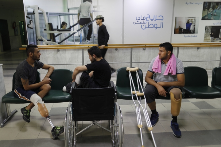 In this Sunday, Oct. 7, 2018 photo, Syrian soldiers who lost their legs while fighting in Syria's war, attend a physical therapy session at the Ahmad Hamish Martyr hospital, in Damascus, Syria. Many Syrian government soldiers, after years of intense fighting, now face a new reality of learning to live without one or more of their limbs, or with other serious disability. The hospital manufactures 60 prosthetic limbs a day, reflecting the high demand in a nation wracked by a bloody civil war. (AP Photo/Hassan Ammar)