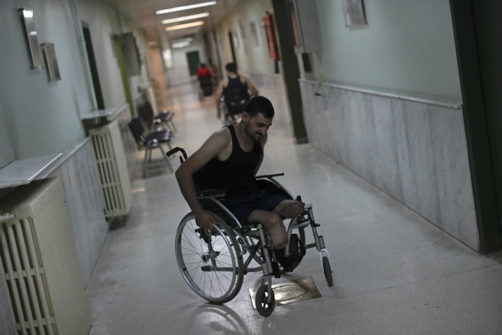 In this Sunday, Oct. 7, 2018 photo, Omar Beik, a 32-year-old soldier from Aleppo, who lost his legs in April when he stepped on a land mine in the final days of the battle for Damascus' eastern suburbs, known as eastern Ghouta, rolls his wheelchair during a physical therapy session at the Ahmad Hamish Martyr hospital in Damascus, Syria. The hospital manufactures 60 prosthetic limbs a day, reflecting the high demand in a nation wracked by a bloody civil war. (AP Photo/Hassan Ammar)