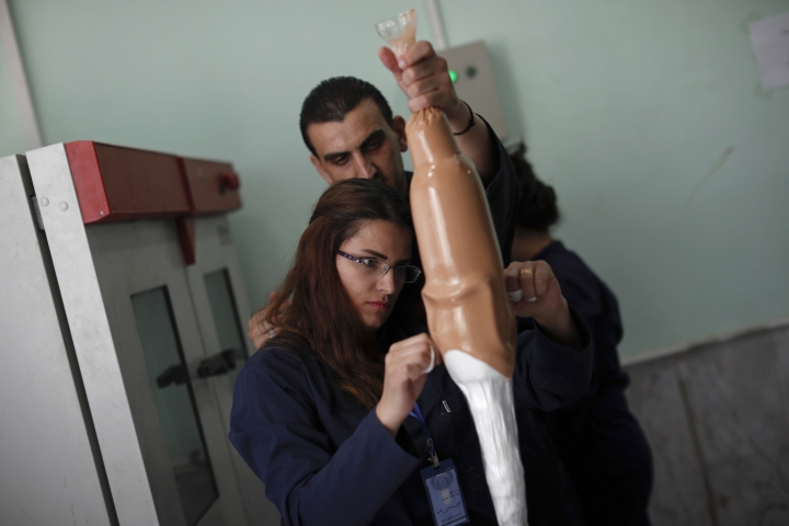 In this Sunday, Oct. 7, 2018 photo, employees of the center for prosthetics and orthotics at the Ahmad Hamish Martyr hospital, work on a form for a prosthetic leg, in Damascus, Syria. The center uses advanced technology to manufacture 60 prosthetic limbs a day, reflecting the high demand in a nation wracked by conflict for the past seven years. (AP Photo/Hassan Ammar)
