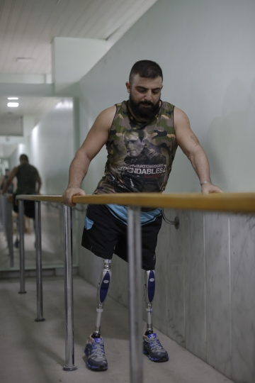 In this Sunday, Oct. 7, 2018 photo, Haidar Hussein, a Syrian soldier who lost his legs while fighting on the front lines in Syria's war, walks on prosthetic legs during a physical therapy session at the Ahmad Hamish Martyr hospital, in Damascus, Syria. Many Syrian government soldiers, after years intense fighting, now face a new reality of learning to live without one or more of their limbs, or with other serious disability. (AP Photo/Hassan Ammar)