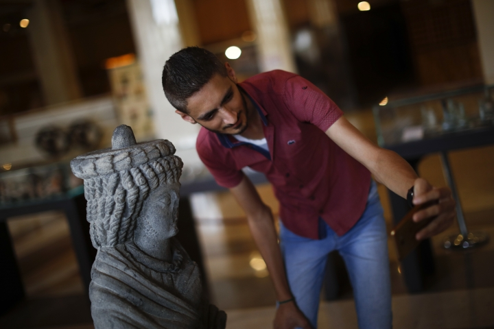 A Syrian man takes a selfie with a statue of a local ruler dating back to the first or second century A.D., that was recovered from an area formerly held by insurgents, that is on display at an exhibition at the Opera House, in Damascus, Syria, Monday, Oct. 8, 2018. The items on display are some of the roughly 20,000 that officials estimate have been recovered since the country's war began in 2011. (AP Photo/Hassan Ammar)