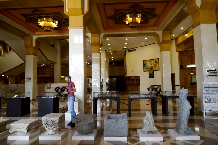 A Syrian man visits an exhibition of hundreds of artifacts were recovered from an area formerly held by insurgents, at the Opera House, in Damascus, Syria, Monday, Oct. 8, 2018. The items on display are some of the roughly 20,000 that officials estimate have been recovered since the country's war began in 2011. (AP Photo/Hassan Ammar)