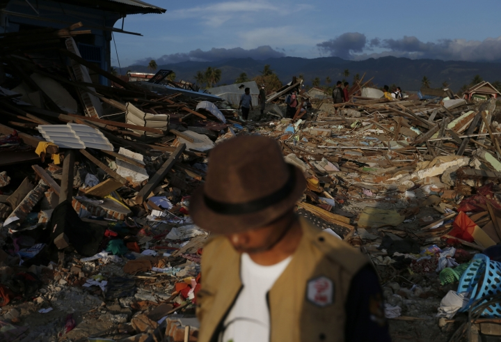 In this Oct. 5, 2018, photo, a man walks on the rubble of houses in the Petobo neighborhood which was wiped out by earthquake-triggered liquefaction in Palu, Central Sulawesi, Indonesia. Many in the decimated village had no idea they were in an area already identified as a high-risk zone for this apocalyptic phenomenon that causes soft ground to liquefy during temblors. The area around Sulawesi island's Palu Bay had been slammed before and was due for another potential perfect storm, capable of unleashing earthquakes, landslides, tsunami waves and soil liquefaction. (AP Photo/Dita Alangkara)