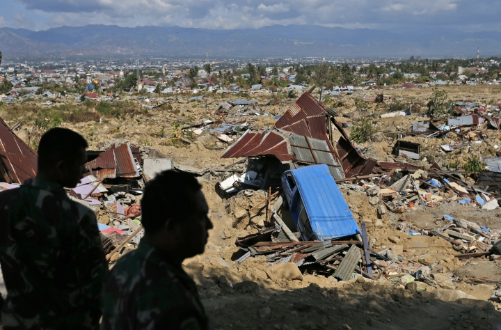 In this Saturday, Oct. 6, 2018, photo, soldiers survey the damage at Balaroa neighborhood which was wiped out by earthquake-triggered liquefaction in Palu, Central Sulawesi, Indonesia. Following the 7.5 magnitude earthquake on Sept. 28, the ground in the area simply lost its strength and turned to mush beneath people's feet, creating mud that acted like quicksand. Humans, houses, cars, and streets were sucked down and covered by a thick carpet of what _ just seconds earlier _ had been solid earth. (AP Photo/Dita Alangkara)